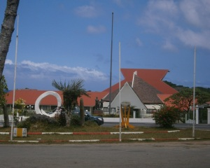 Vanuatu's Parliament house in the background. In the foreground is a carved out Pig's Tusk - a symbol of wealth in Vanuatu.