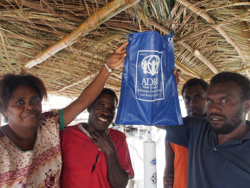 Helen, with the families which share the ADRA water filter.